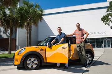 "Dr. Mattia Prosperi and Dr. Volker Mai with the Mini Cooper that is being used to collect insect and insect ""splats"" as part of the UF HealthStreet community engagement program."